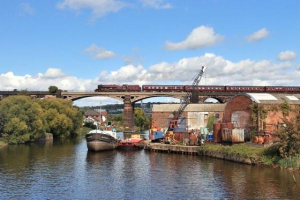 A steam train going over a bridge